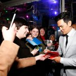 John Cho signs autographs for fans
